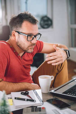 Man in red shirt telecommuting at home office