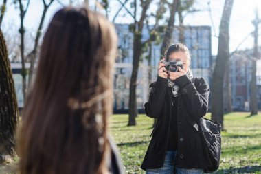 Woman taking a photo with old analog camera in spring park