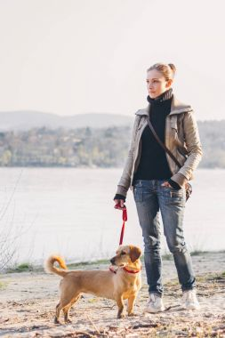 Woman and her mixed breed dog enjoining by the river.