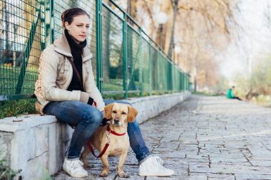 Woman sitting and resting by the fence with her dog