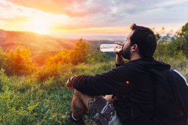 Man with beard drinking water from plastic bottle and enjoying mountain sunset.