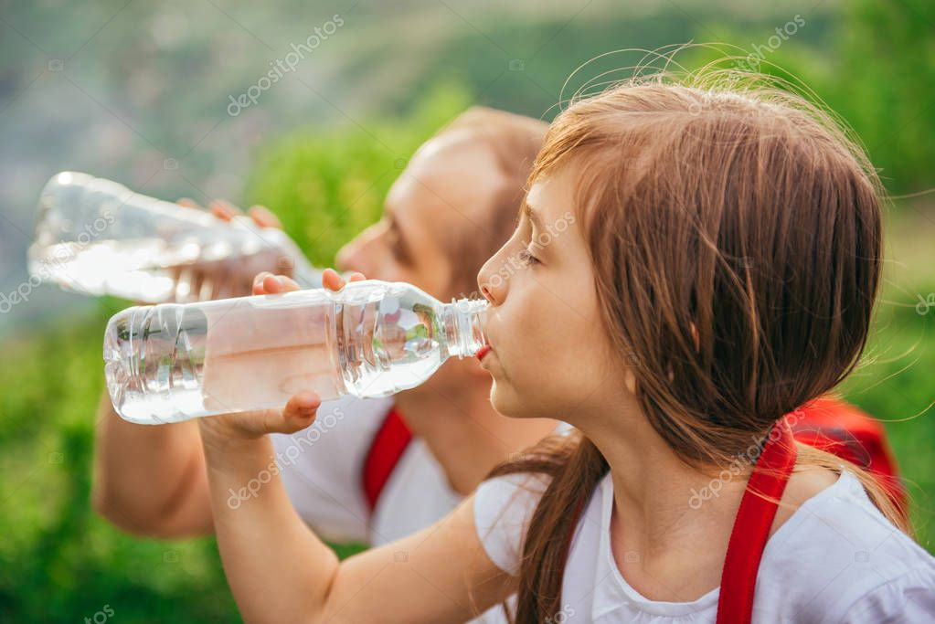 Daughter and father having a break and drinking water from pet bottle.