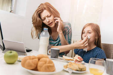 Mother working at home in the kitchen with daughter