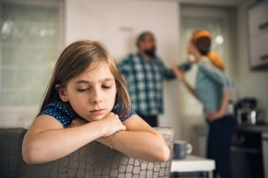 Traumatized daughter listening parents arguing at home