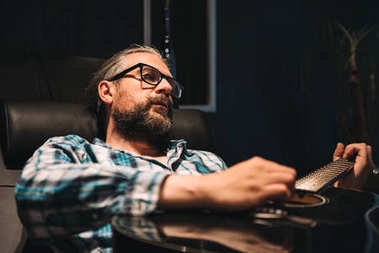 Man with glasses and beard sitting in leather sofa and playing guitar at home