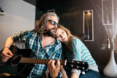 Romantic man with glasses and beard playing guitar for his woman