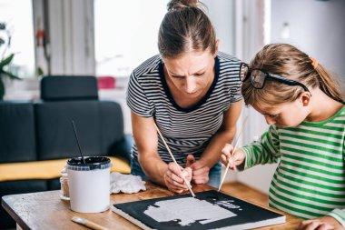 Mother and daughter together painting canvas at home