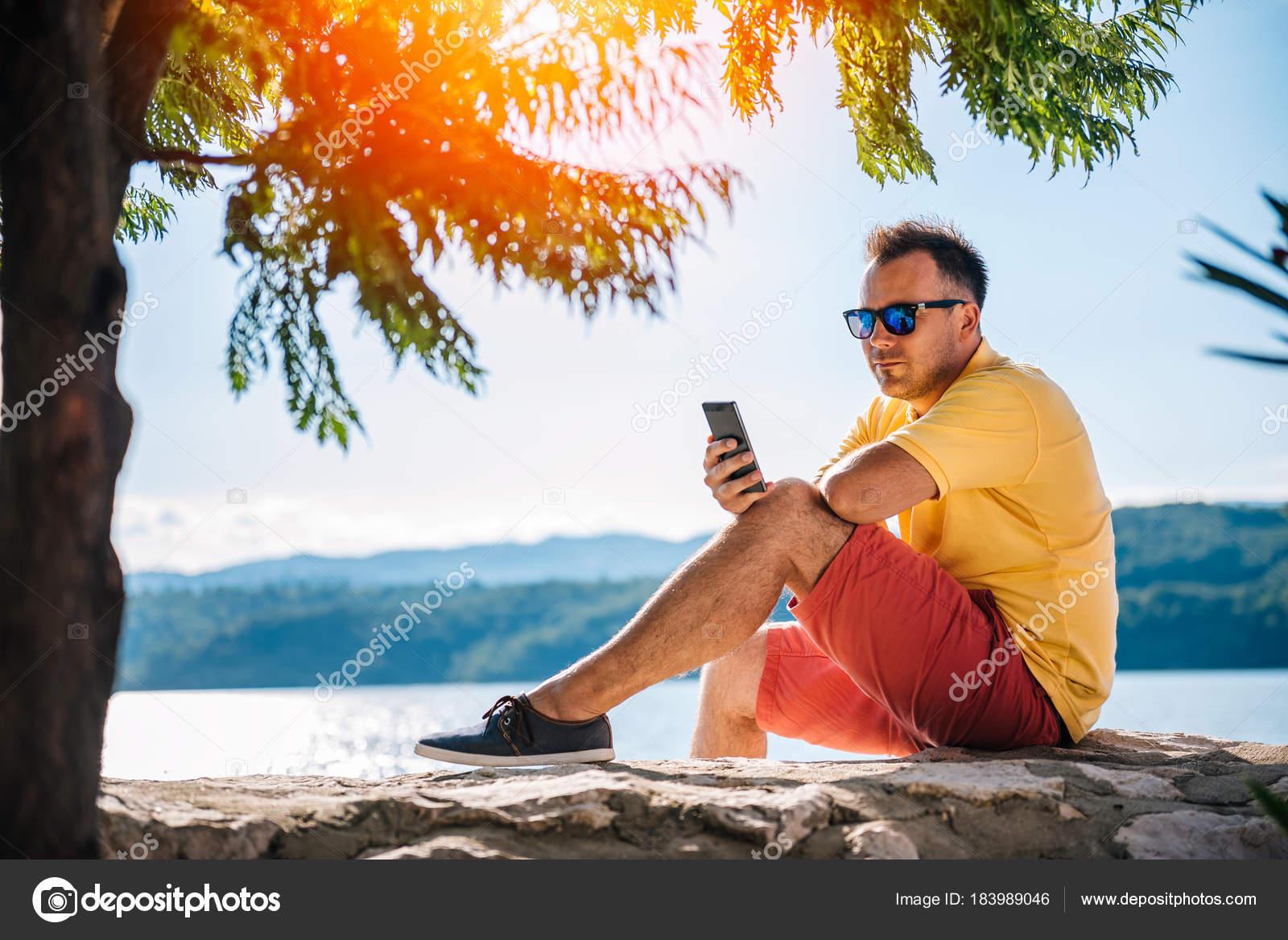 Homem Camisa Amarela Óculos Sol Sentado Cais Pedra Usando Telefone —  Fotografia de Stock f544750f73