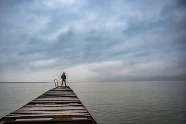 Man standing on a old wooden dock in stormy weather and looking at the distance