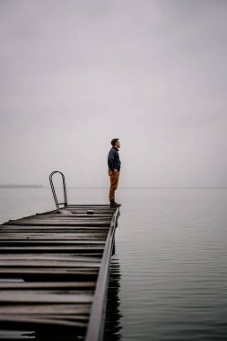 Man standing on a old wooden dock and looking at the distance