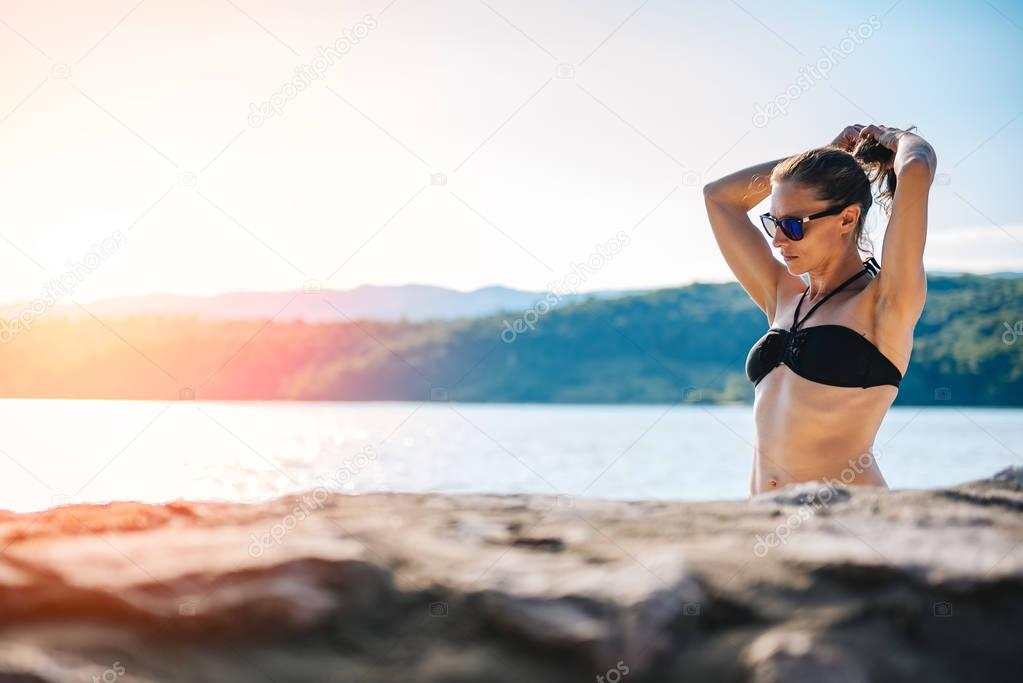 Woman in black bikini standing on a beach and fixing her hair