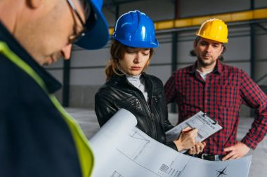 Site Inspector making inspection report in big industrial hall and talking with Construction workers