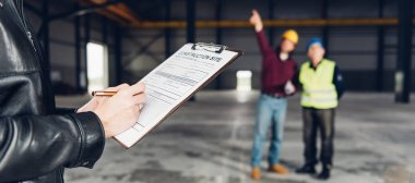 Site Inspector making inspection report in big industrial hall
