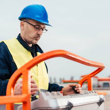 Operator In Safety Helmet controlling Straight Boom Lift