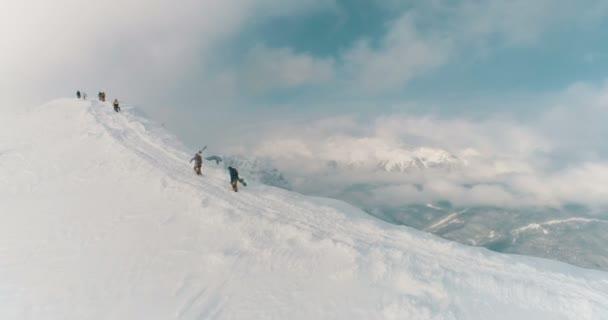 Letecký pohled na lyžařů a turistů přes horský hřeben skrz mraky