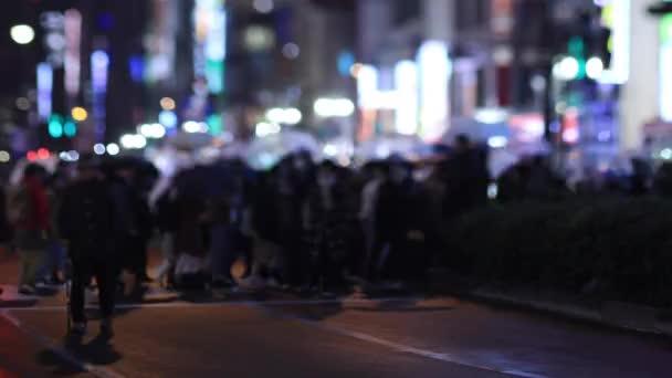 Walking people at the crossing in Shinjuku Tokyo rainy day at night