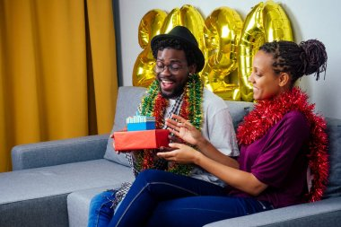 multinational couple in love sitting on sofa exchanging presents on Christmas eve in living room