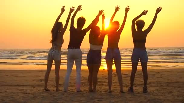 Group of happy people sits on empty sunset beach and wave to sun