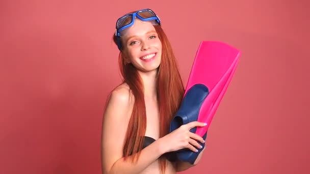 rothaarige Ingwerfrau im rosafarbenen Studiohintergrund mit Wasserbrille, Taucherbrille und schwarzem Badeanzug, sie hält Schwimmflossen in der Hand, Reisekonzept der Krankenversicherung