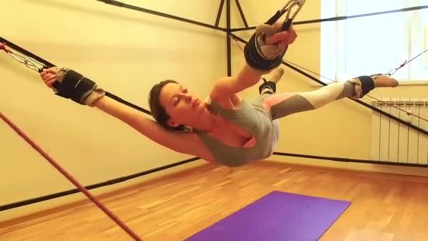 Sportos fiatal kaukázusi nő csinál nyújtás gyakorlatok teljes test izmok edzés nyújtás aerob aerob heveder tornaterem, yogi mat