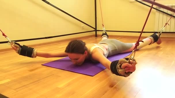 Sporty young caucasian woman doing stretching exercises of full body muscles workout on stretch aerobic aero strap in gym,yogi mat