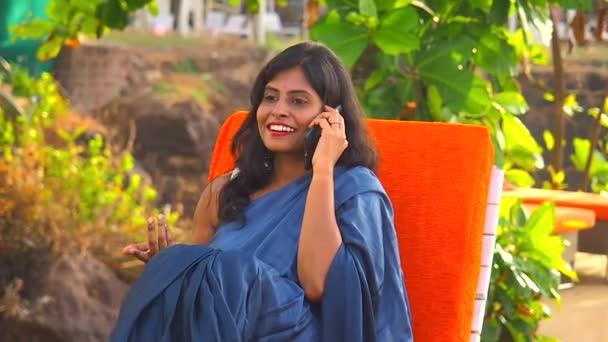 Indianerin im blauen Sari telefoniert am Tropenstrand von Goa