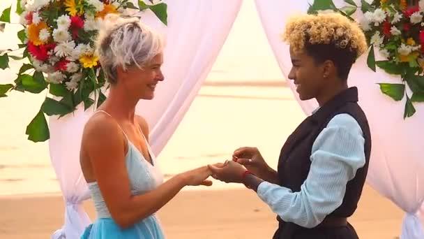 afro-amerikai női vőlegény fekete öltönyben és kaukázusi menyasszony ruhában ceremónián gyűrűt cserél a kezében trópusi strandon az esküvői flover boltív alatt