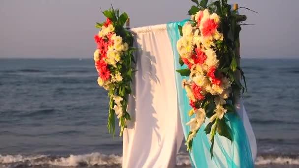 Krásný letní svatební obřad venku. Svatební oblouk z lehké látky a bílé a růžové květy na moři