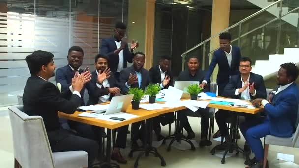 success international group of ten excited young business team throwing away papers and hands shake