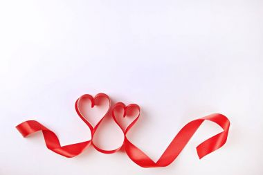 Isolated silk red ribbon lined in heart shape on solid white background. Festive decoration. Mother's, Women's, Wedding, Happy st Valentines Day concept, 14th February. Backdrop, copy space, close up stock vector
