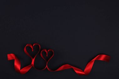 Isolated silk red ribbon lined in heart shape on solid black background. Festive decoration. Mother's, Women's, Wedding, Happy st Valentines Day concept, 14th February. Backdrop, copy space, close up stock vector
