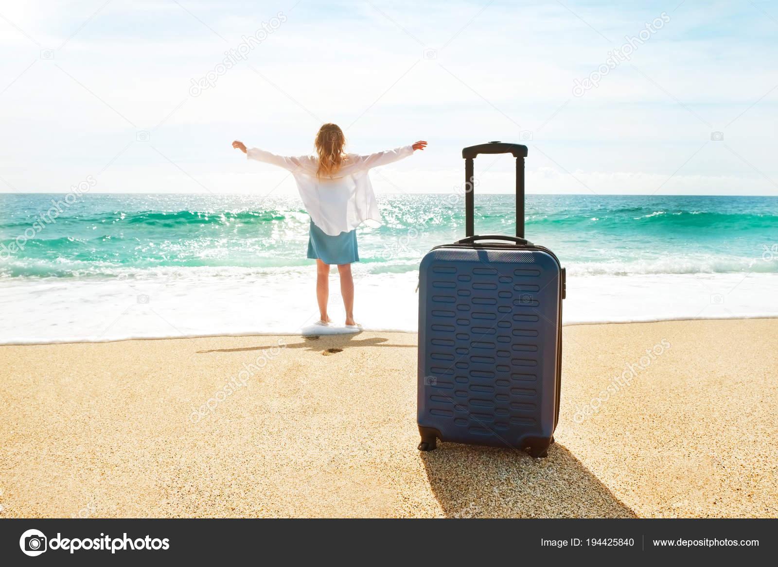 d6b0ad6988f7 Giovane donna con il suo bagaglio valigia sulla bellissima spiaggia di  sabbia con vista sul mare in giornata di sole. Donna di hipster in camicia  di cotone ...