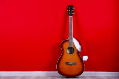 Christmas music concept. Acoustic guitar with steel strings and santa claus hat.