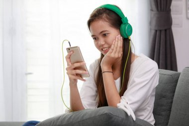 Young Asian girl listening to music with headphone and smarthpho