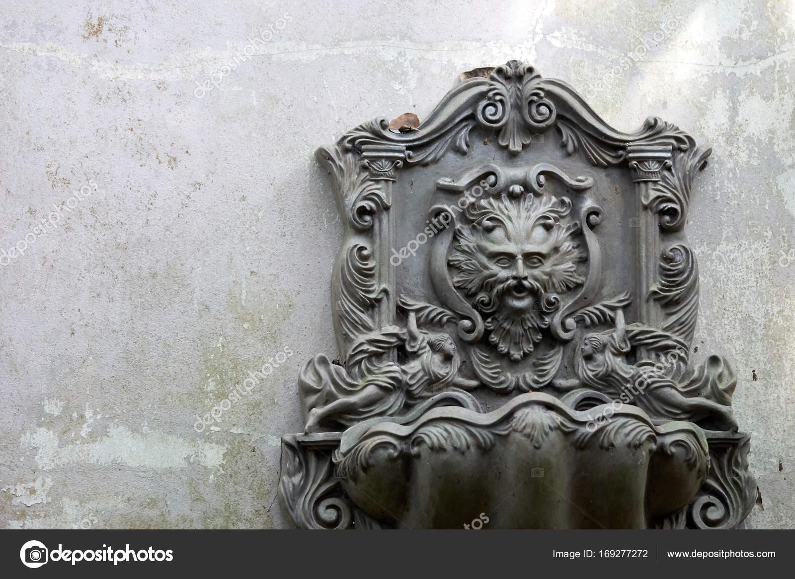 Oude leeuw hoofd fontein die is gemonteerd op een muur wit grijs