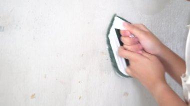 Asian female hand Making and repairing the wall. To prepare a new paint. as background interior decoration concept with copy space.