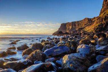 Talisker Bay boulders and cliffs at sunset