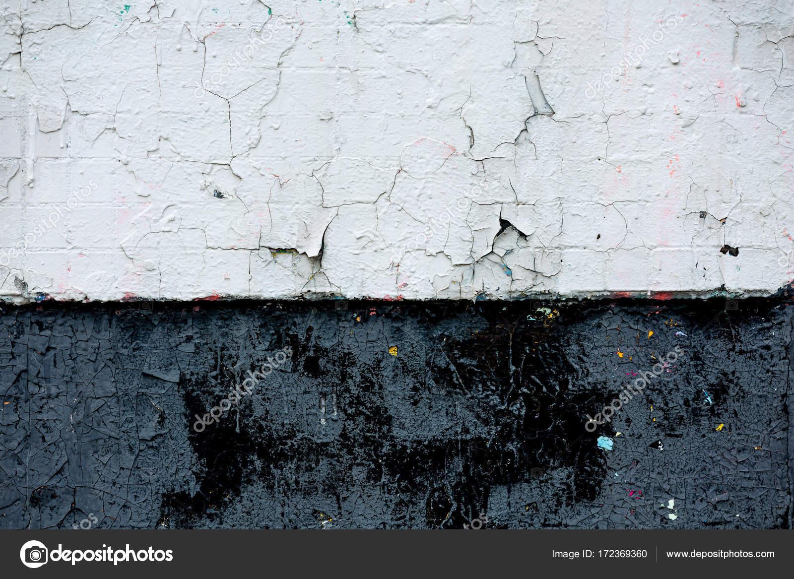 Parete nera e whitw di piccole piastrelle in vernice con le crepe