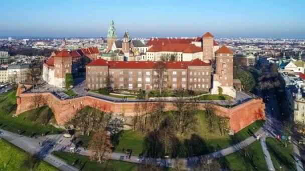 Castello reale di Wawel e la Cattedrale gotica a Cracovia, in Polonia, con la rinascimentale Cappella di Sigismondo con cupola dorata, fortificati pareti, iarda, parco e turisti. Vista aerea al tramonto in inverno