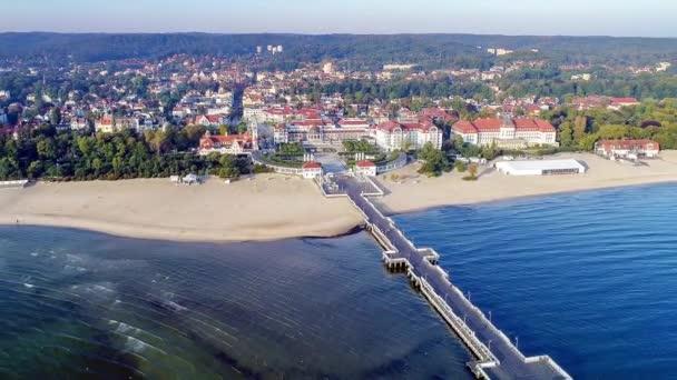 Sopoty středisko v Polsku. Dřevěné molo (Molo) s promenádou, marina, jachty, pirátské turistické lodi, pláž, starý maják, lázně, hotely a rekreační infrastrukturu. Letecká 4k odhalení video při východu slunce