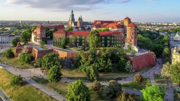 Krakow, Poland. Wawel royal Castle and Cathedral, Vistula River, park, promenade and walking people. Cracow old city with historic churches in the background. Aerial 4K flyby video at sunset in spring