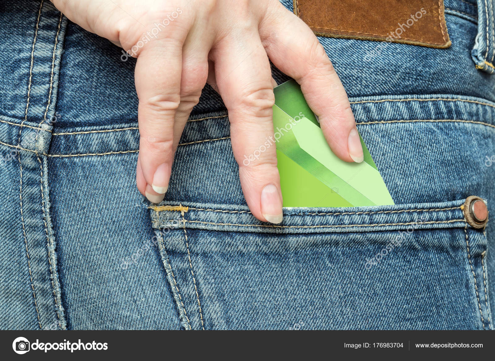 417708995 The hand pulls out a bank card from the pocket of the jeans ...