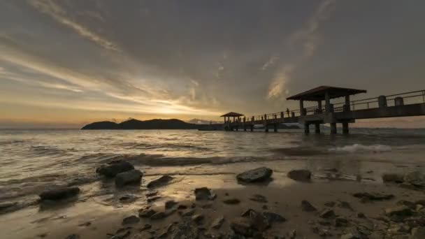 Timelapse sunset over a rocky stone seaside at Batu Kawan,