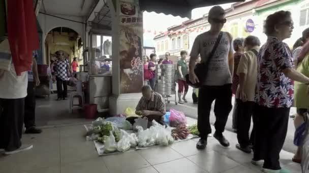Obchodník prodávají zeleninu na podlaze na ranní trh