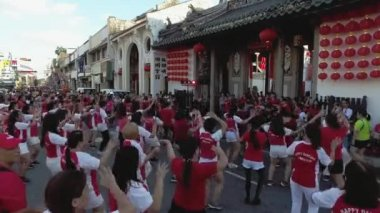 A group women wear red shirt dance in front of temple during chinese new year