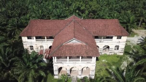 Aerial view colonial building 99 door mansion in overgrown oil palm estate.