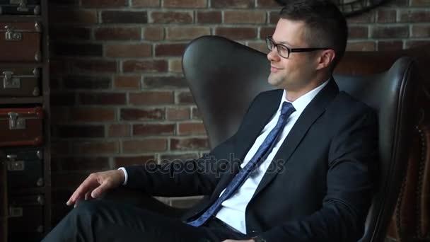 Úspěšné pohledný mladý podnikatel v křesle