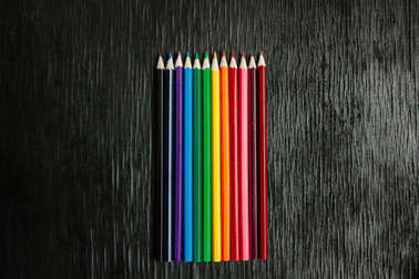 Many colored pencils on a black background. New pencils