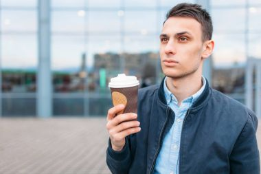 a man walks around the city and drinking coffee from a paper Cup, a handsome guy walks around and resting, the guy on the background of a modern building, office