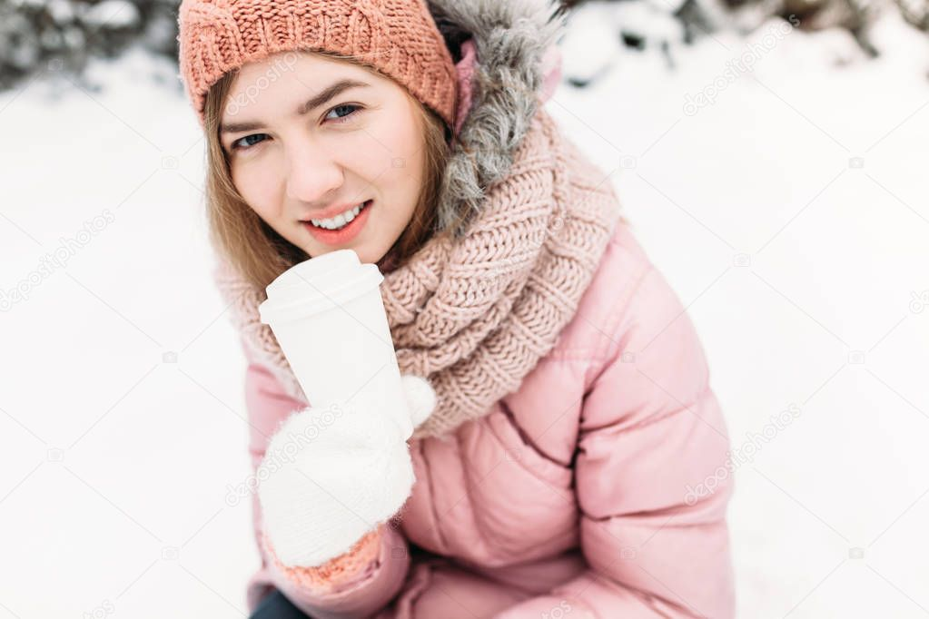 Portrait of a beautiful young girl in white knitted mittens, outdoors, holding a paper Cup with a hot beverage, bright winter day.the woman smiles and is happy, close-up, Trees in first snow in the.